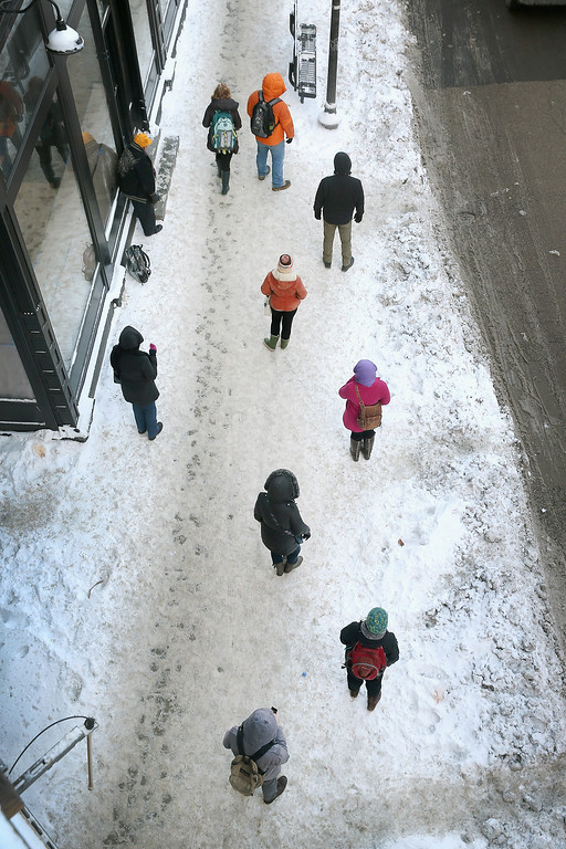 . Commuters wait on a frozen sidewalk in below zero temperatures for a bus to arrive on January 7, 2014 in Chicago, Illinois. Chicago is experiencing its third consecutive day of below zero temperatures.  (Photo by Scott Olson/Getty Images)