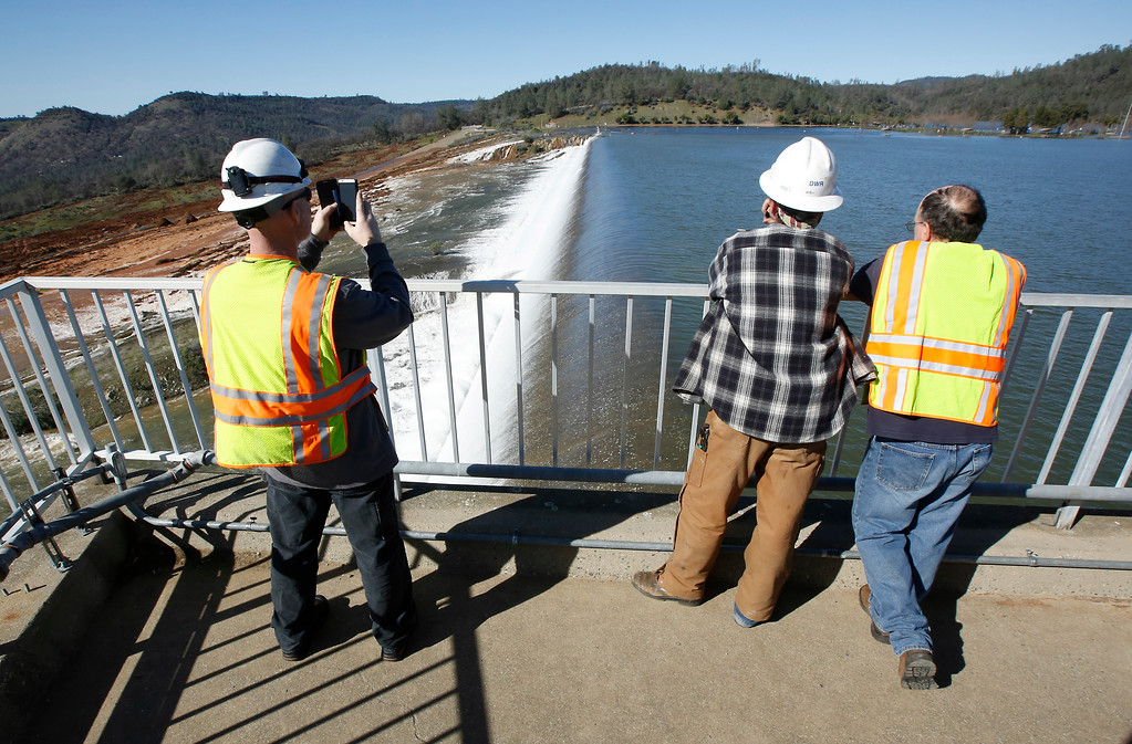 . Jason Newton, left, of the Department of Water Resources, takes a picture of water going over the emergency spillway at Oroville Dam Saturday, Feb. 11, 2017, in Oroville, Calif. Water started flowing over the spillway,at the nation\'s tallest dam, for the first time Saturday morning after erosion damaged the Northern California dam\'s main spillway.(AP Photo/Rich Pedroncelli)