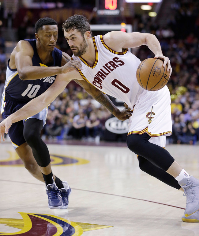 . Cleveland Cavaliers\' Kevin Love (0) drives past Memphis Grizzlies\' Troy Williams (10) in the first half of an NBA basketball game, Tuesday, Dec. 13, 2016, in Cleveland. (AP Photo/Tony Dejak)