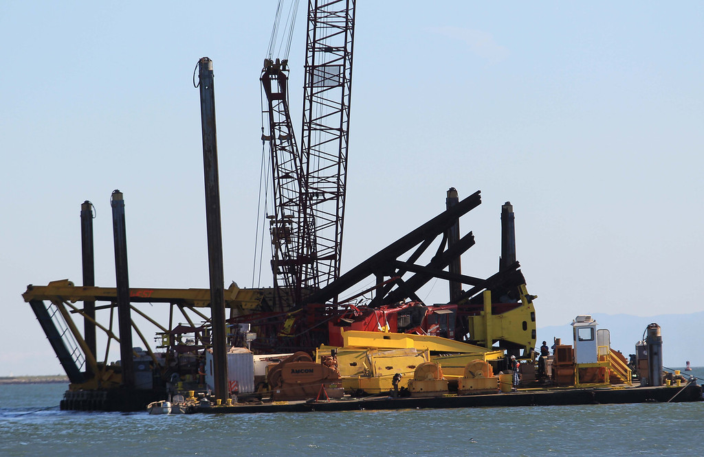. Workers inspect the scene after a barge crane collapsed while removing iron falsework from the new Oakland-San Francisco Bay Bridge project in San Francisco, Calif. on Thursday, Feb. 21, 2013. No one was injured in the incident. (Jane Tyska/Staff)