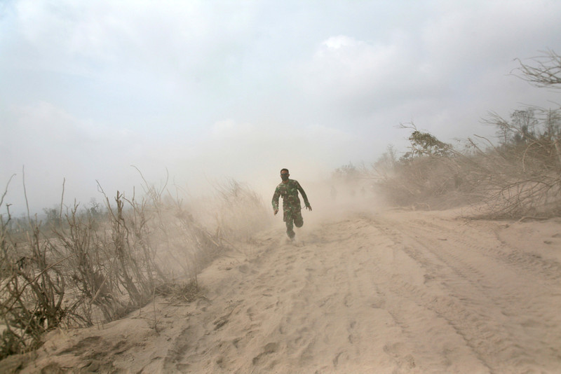 . An Indonesian soldier runs on ash-covered road as he and his team search victims of the eruption of Mount Sinabung in Suka Meriah, North Sumatra, Indonesia, Saturday,  Feb. 2, 2014. Mount Sinabung erupted Saturday killing more than a dozen of people. (AP Photo/Binsar Bakkara)