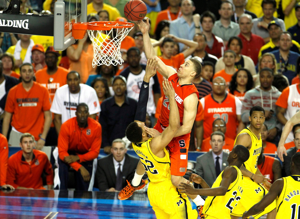 . Syracuse Orange guard Brandon Triche (top) is called for a charge on Michigan Wolverines forward Jordan Morgan (52) in the final seconds of the second half of their NCAA men\'s Final Four basketball game in Atlanta, Georgia April 6, 2013.  REUTERS/Tami Chappell