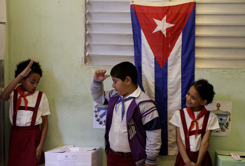 . Students raise their hands confirming a voter is properly casting his ballot at a polling station during parliament elections in Havana, Cuba, Sunday, Feb. 3, 2013. More than 8 million islanders are eligible to vote and will approve 612 members of the National Assembly and over 1,600 provincial delegates. (AP Photo/Franklin Reyes)