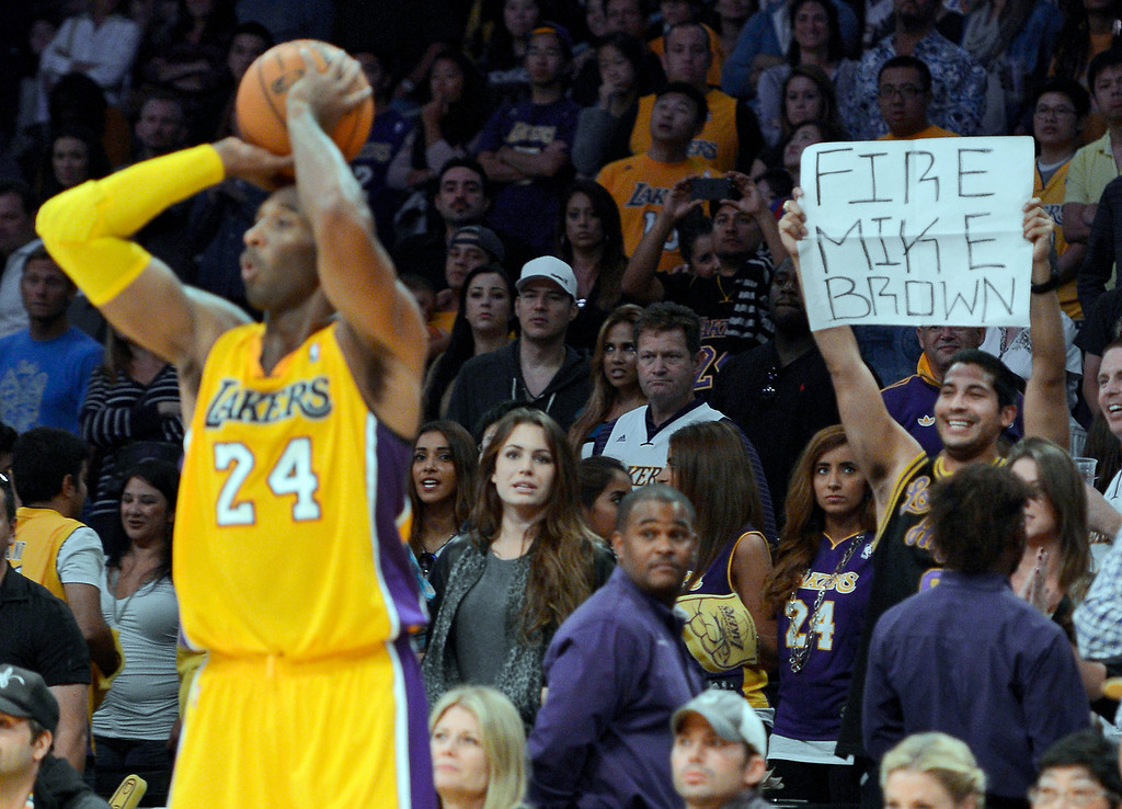 . In this photo taken Oct. 21, 2012, Los Angeles Lakers guard Kobe Bryant passes the ball as a fan holds up a sign regarding Lakers coach Mike Brown during the second half of a preseason NBA basketball game against the Sacramento Kings in Los Angeles. The Lakers fired Brown on Friday, Nov. 9, 2012, after a 1-4 start in his second season in charge. (AP Photo/Mark J. Terrill)
