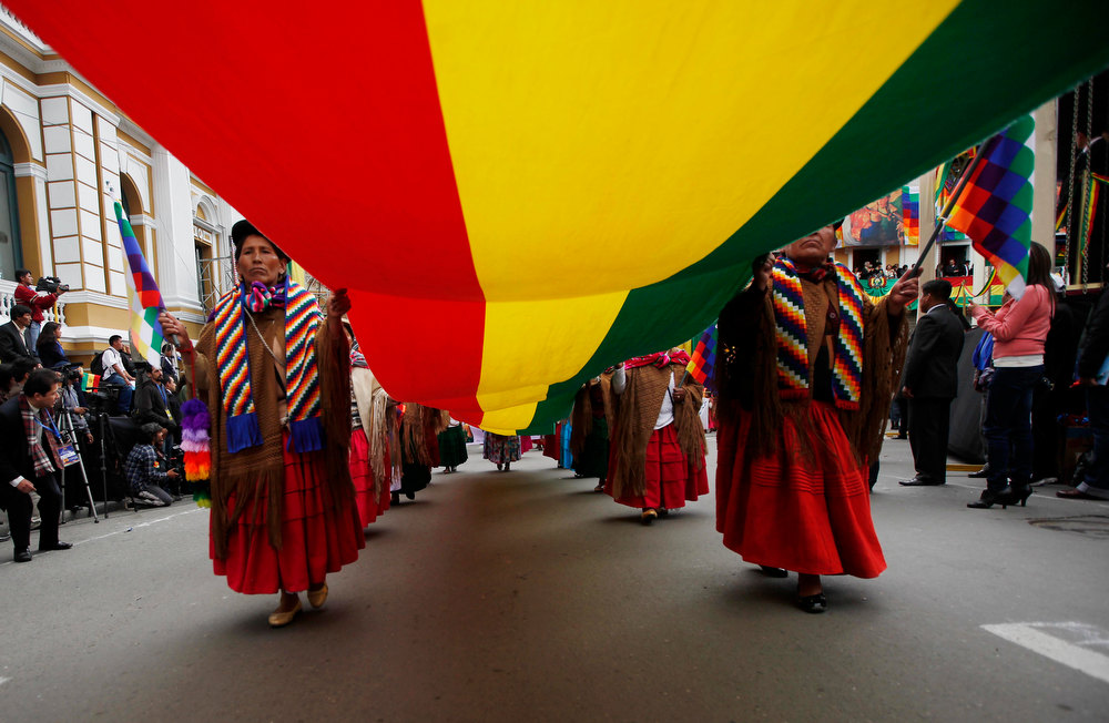 Description of . Women carry a Bolivian flag during a parade after Bolivia's President Evo Morales, not in picture, delivered his state of the nation address in La Paz, Bolivia, Tuesday, Jan. 22, 2013. Morales is marking his seventh year as president. (AP Photo/Juan Karita)