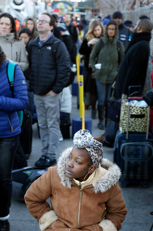 . Alona Johnson of Queens, N.Y., waits in line to travel to Baltimore, M.D., to visit with her dad for Thanksgiving in New York, Wednesday, Nov. 23, 2016. Almost 49 million people are expected to travel 50 miles or more for the holiday, the most since 2007, according to AAA.  (AP Photo/Seth Wenig)