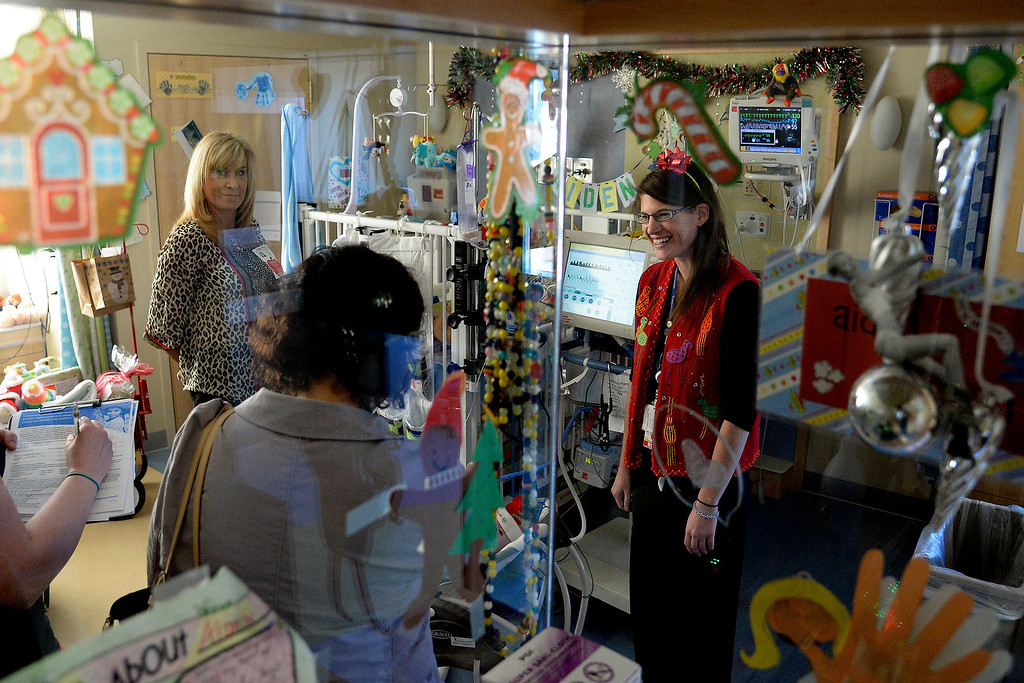 . AURORA, CO - DECEMBER 25: Nurse Sarah Hodgin visits with the family of baby Aiden Schmitt during her shift in the NICU. Nurses and other hospital staff work on Christmas day at Children\'s Hospital on Wednesday, December 25, 2013. (Photo by AAron Ontiveroz/The Denver Post)
