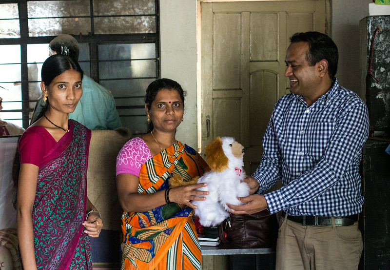Praveen receives a stuffed turtle at the Global Communities center in Ramoshi Ali, a Pune slum.