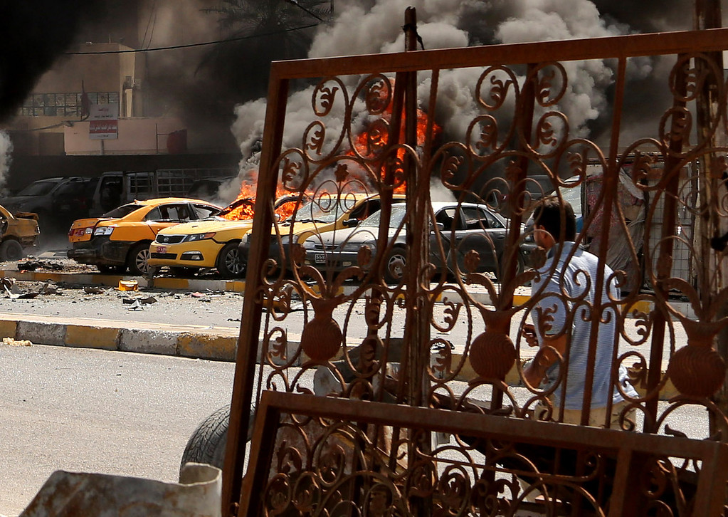 . An Iraqi man looks at burning vehicles moments after one in a series of bombs hit the Shiite stronghold of Sadr City, in Baghdad, Iraq, Tuesday, May 13, 2014.  (AP Photo/Karim Kadim)