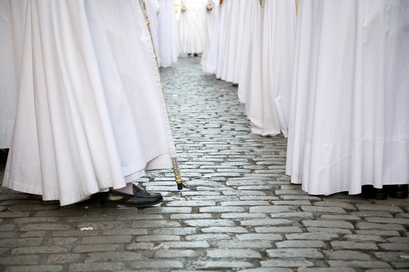 The white habits of penitents on the tiling floor, Palm Sunday, Seville, Spain