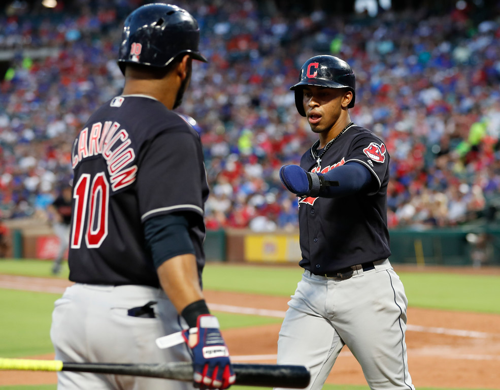 . Cleveland Indians\' Francisco Lindor, right, celebrates his run scored with Edwin Encarnacion on a single hit by Michael Brantley against the Texas Rangers during the fifth inning of a baseball game, Saturday, July 21, 2018, in Arlington, Texas. (AP Photo/Jim Cowsert)