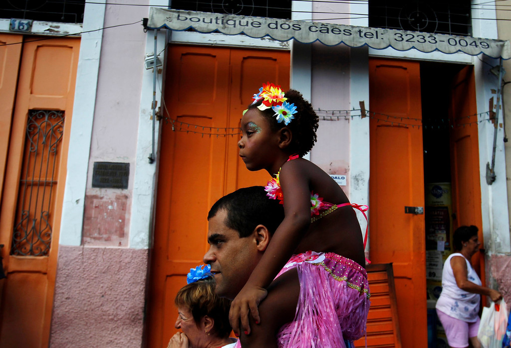". A reveller carrying a child takes part in an annual block party known as the ""Ceu na Terra\"" (or Sky on Earth), one of the many carnival parties to take place in the neighborhoods of Rio de Janeiro February 2, 2013. REUTERS/Pilar Olivares"