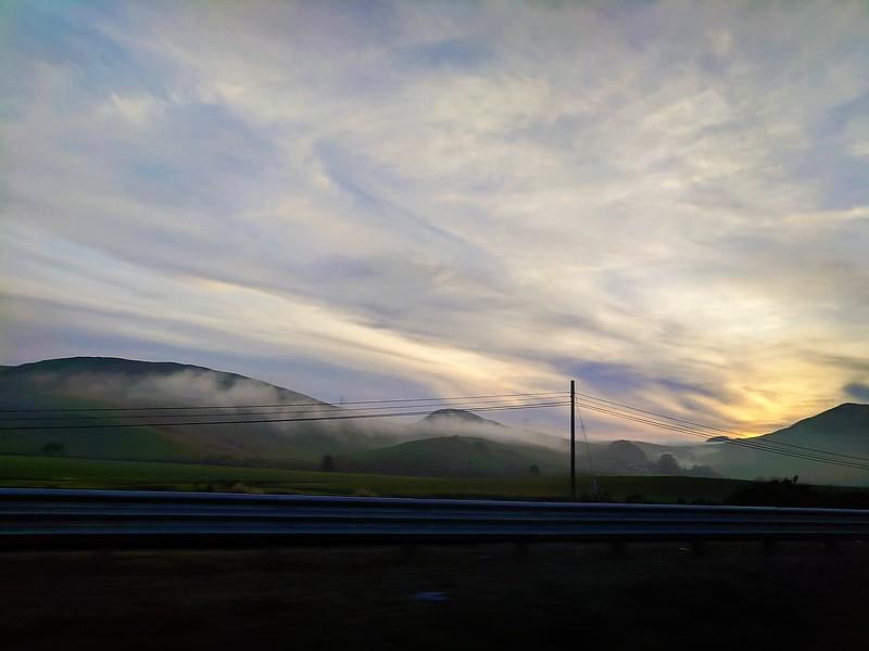 fog around hills adjacent to highway