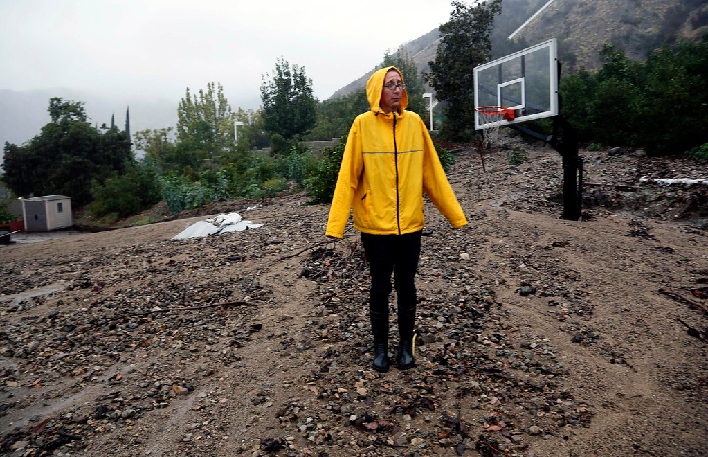 . Homeowner Amanda Heinlein stands on a mud landslide covering a basketball court near her house in Azusa, Calif., Friday, Dec. 12, 2014.   A soaking storm swept into  California, causing several mudslides, flooding streets and cutting power to tens of thousands Friday after lashing the rest of the state with much-needed rain.   (AP Photo/Nick Ut)