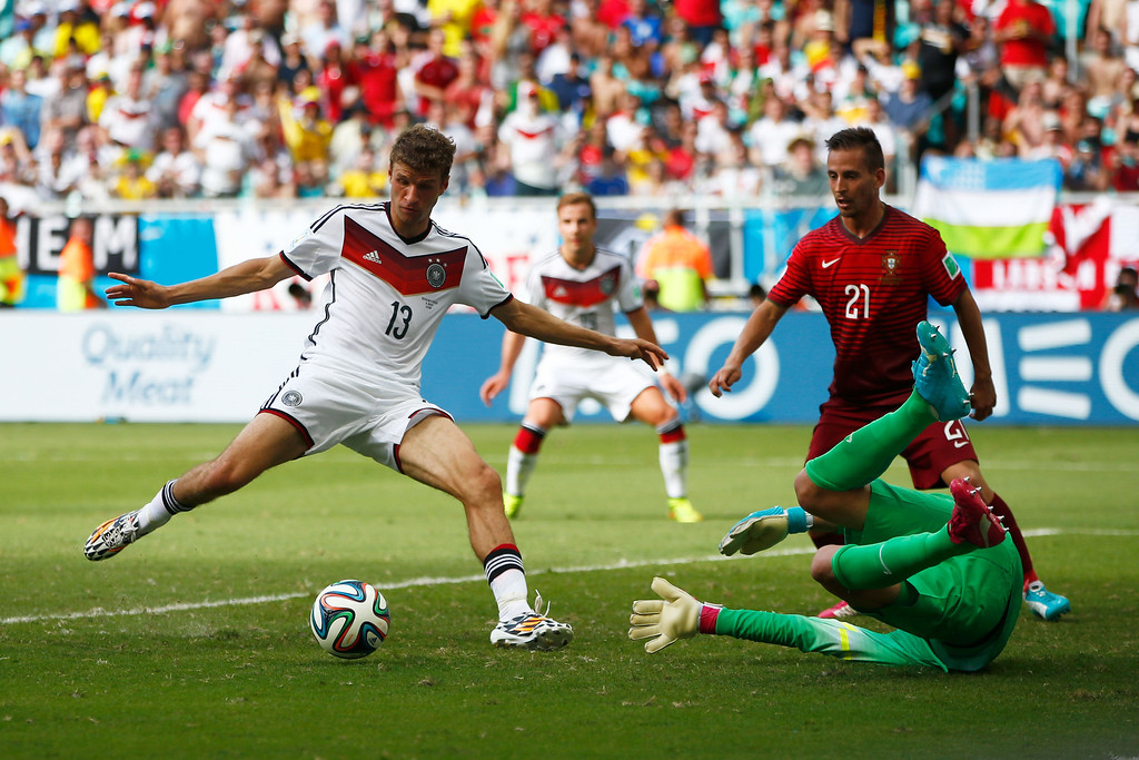 . Thomas Mueller of Germany shoots and scores his team\'s fourth goal and completes his hat trick past Rui Patricio of Portugal during the 2014 FIFA World Cup Brazil Group G match between Germany and Portugal at Arena Fonte Nova on June 16, 2014 in Salvador, Brazil.  (Photo by Phil Walter/Getty Images)