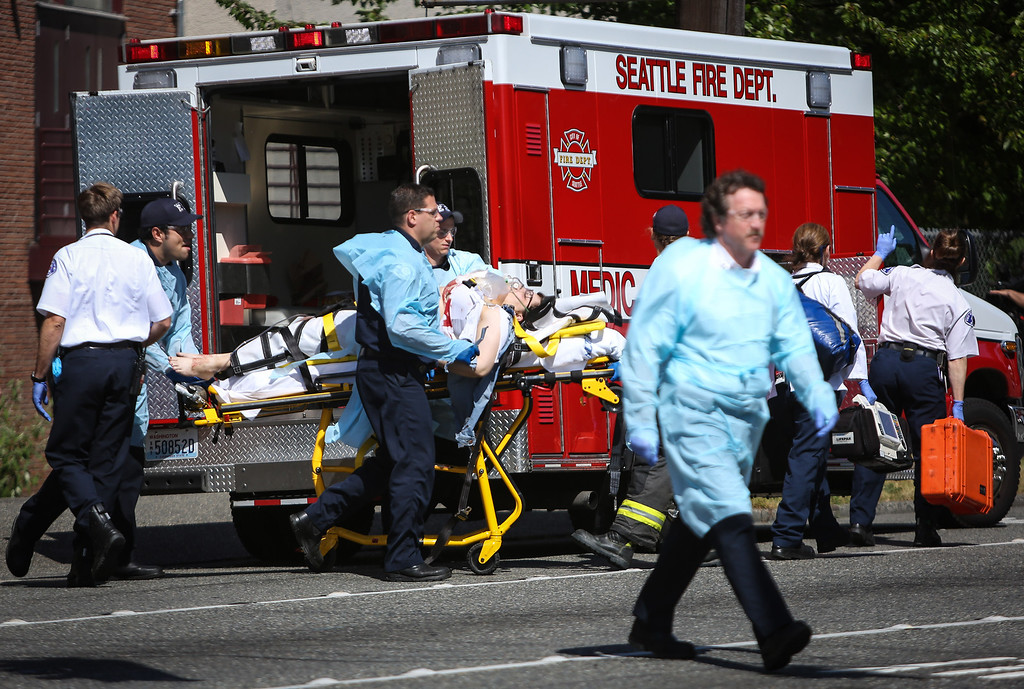 . Medics wheel away a person shot at Seattle Pacific University on Thursday, June 5, 2014, in Seattle. A lone gunman armed with a shotgun opened fire Thursday in a building at a small Seattle university, fatally wounding one person before a student subdued him with pepper spray as he tried to reload, Seattle police said. (AP Photo/seattlepi.com, Joshua Trujillo)
