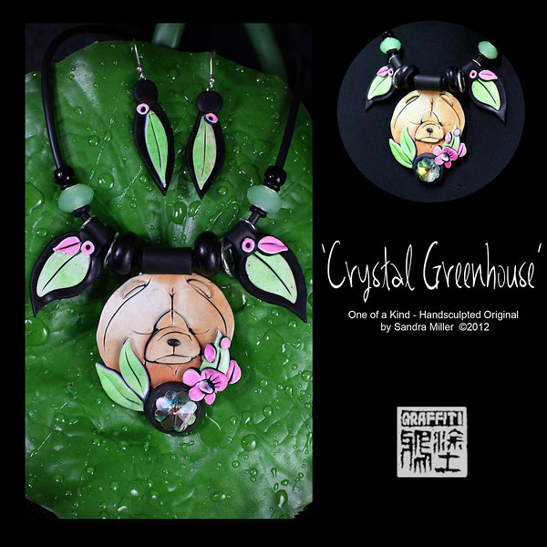 """CRYSTAL GREENHOUSE-  CLICK HERE TO VIEW VIDEO DESCRIPTION IN A NEW WINDOW      CRYSTAL GREENHOUSE  is one of my 3-D watercolor designS that features a 1920s flower shape Swarovski Crystal down below her chin      They face on this chow is absolutely gorgeous ....look at that pretty pretty muzzle. I sculpted her and the floral elements in white  and then blushed them in layers and layers of color which give an almost airbrushed effect.         The entire head is surrounded by hand sculpted orchids and leaves, and I echoed that same theme up in the handmade leaf beads  on the necklace. They are also 2 wonderful opaque green crystals that flank the leaf beads with matching earrings as well      The beads on the neoprene cord have little tiny disks that slide up and down so you can wear the accents at the level of your neck you prefer.      This necklace and earring set is light as a feather..... you hardly know you're wearing them!  She comes in her own presentation/travel case so she can come to the National with you!!  PENDANT MEASURES   2 x 2 3/4"""" Neoprene cord is finished at the back with chain and adjusts from 16-20"""" long.  EARRINGS MEASURE 1 1/4"""""""