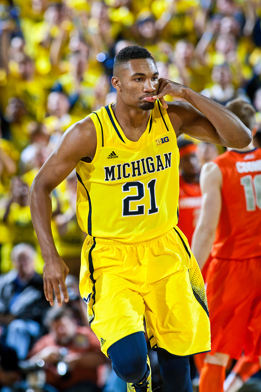 . Michigan guard Zak Irvin (21) reacts after scoring a basket in the first half of an NCAA college basketball game against Syracuse at Crisler Center in Ann Arbor, Mich., Tuesday, Dec. 2, 2014. (AP Photo/Tony Ding)