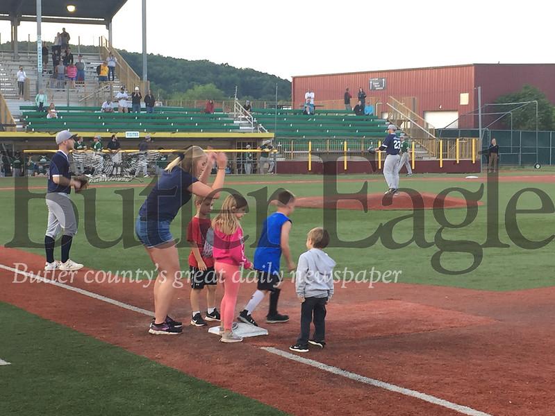 Cutline: Pullman Park staffer Mackenzi Popovich, left, aids children prior to running the bases during the seventh-inning stretch at a recent Butler BlueSox game.Derek Pyda photo  0619_spo_pullman2