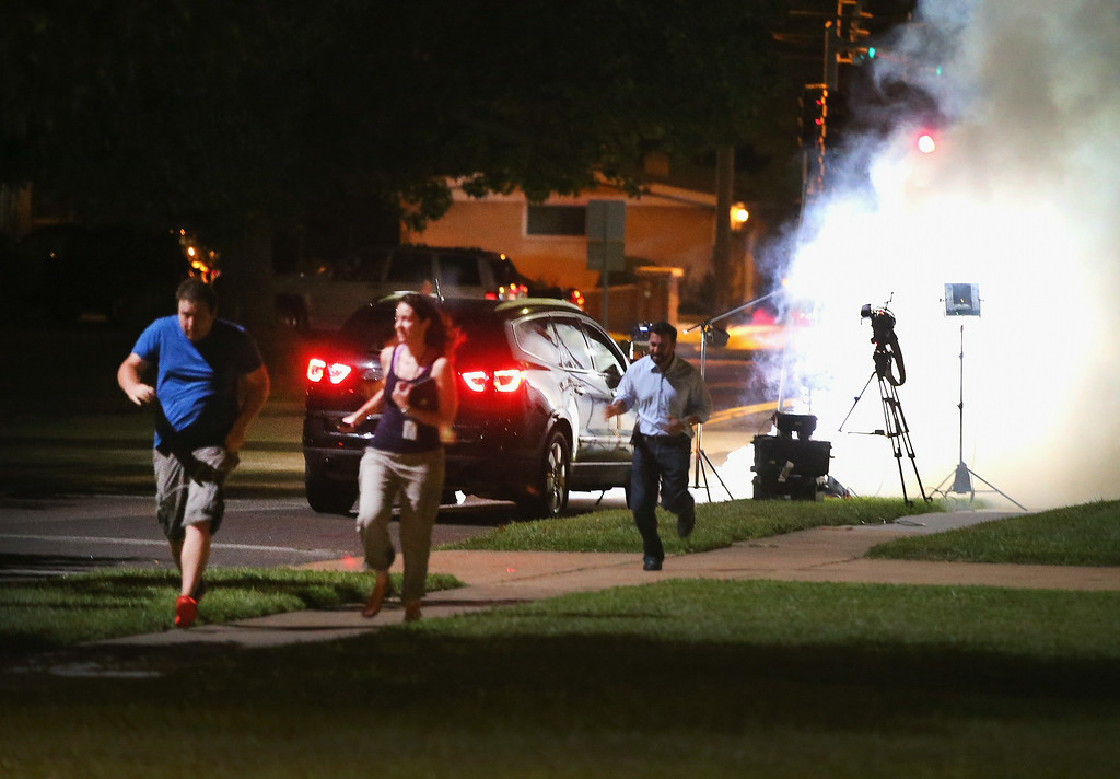 . An Al Jazeera television crew, covering demonstrators protesting the shooting death of teenager Michael Brown, scramble for cover as police fire tear gas into their reporting position on August 13, 2014 in Ferguson, Missouri. Brown was shot and killed by a Ferguson police officer on Saturday. Ferguson, a St. Louis suburb, is experiencing its fourth day of violent protests since the killing.  (Photo by Scott Olson/Getty Images)