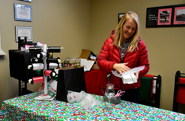 11/24/2018 Mike Orazzi | Staff Employee Karen Zoccoli wraps a gift for a customer at Good Cause Gifts on Main Street in Berlin on Saturday.