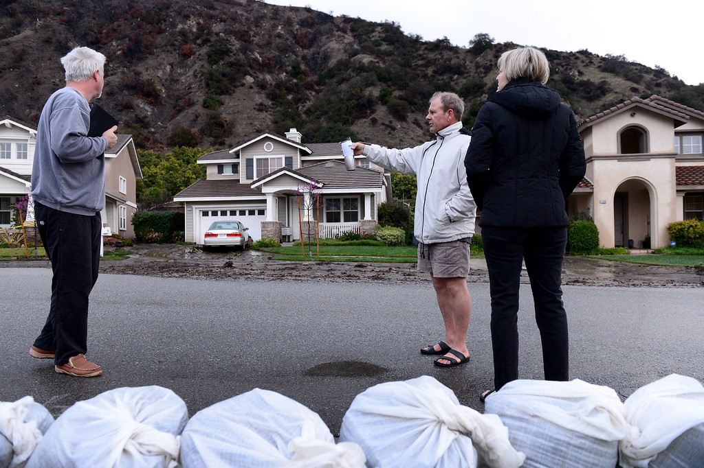 . Dennis and Joann Sanderson walk along their Ridge View Drive street in Azusa early Saturday morning, March 1, 2014 as they stop to talk to neighbor Mark Bryan. The Sanderson\'s stayed behind mandatory evacuation orders. The neighborhood sits below the Colby Fire burn area. (Photo by Sarah Reingewirtz/Pasadena Star-News)