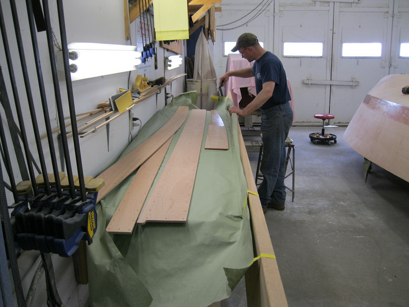 Applying epoxy to the planks before installing them on the boat.