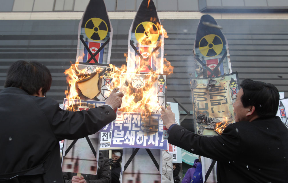 Description of . South Korean conservative protesters burn anti-North Korea placards during a rally demonstrating against North Koreas nuclear test on February 12, 2013 in Seoul, South Korea. North Korea confirmed it had successfully carried out an underground nuclear test as a shallow earthquake with a magnitude of 4.9 was detected by several international monitoring agencies. South Korea and Japan both assembled an emergency meeting of their respective national security teams after the incident.  (Photo by Chung Sung-Jun/Getty Images)