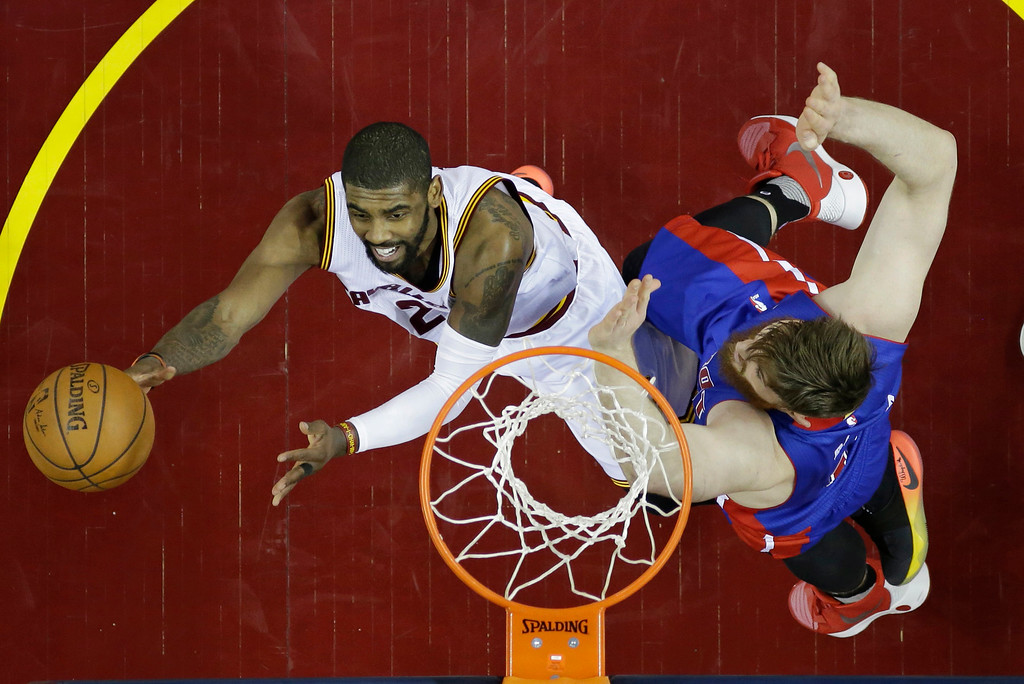 . Cleveland Cavaliers\' Kyrie Irving, left, drives to the basket against Detroit Pistons\' Aron Baynes (12), from Australia, in the first half in Game 1 of a first-round NBA basketball playoff series, Sunday, April 17, 2016, in Cleveland. (AP Photo/Tony Dejak)