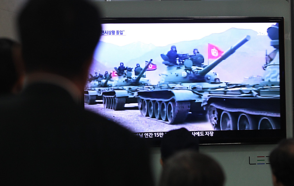 """. People watch a news report showing North Korean army tanks at Seoul Railway Station in Seoul, South Korea, Saturday, March 30, 2013. North Korea warned Seoul on Saturday that the Korean Peninsula was entering \""""a state of war\"""" and threatened to shut down a factory complex that\'s the last major symbol of inter-Korean cooperation. (AP Photo/Ahn Young-joon)"""