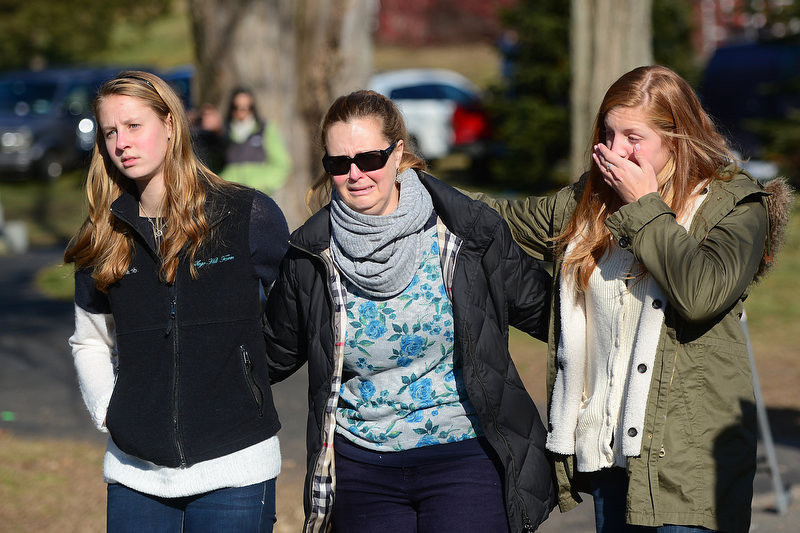 . Residents leave after paying a flower tribute to the victims of an elementary school shooting in Newtown, Connecticut, on December 15, 2012. A young gunman slaughtered 20 small children and six teachers on December 14 after walking into a school in an idyllic Connecticut town wielding at least two sophisticated firearms.      EMMANUEL DUNAND/AFP/Getty Images