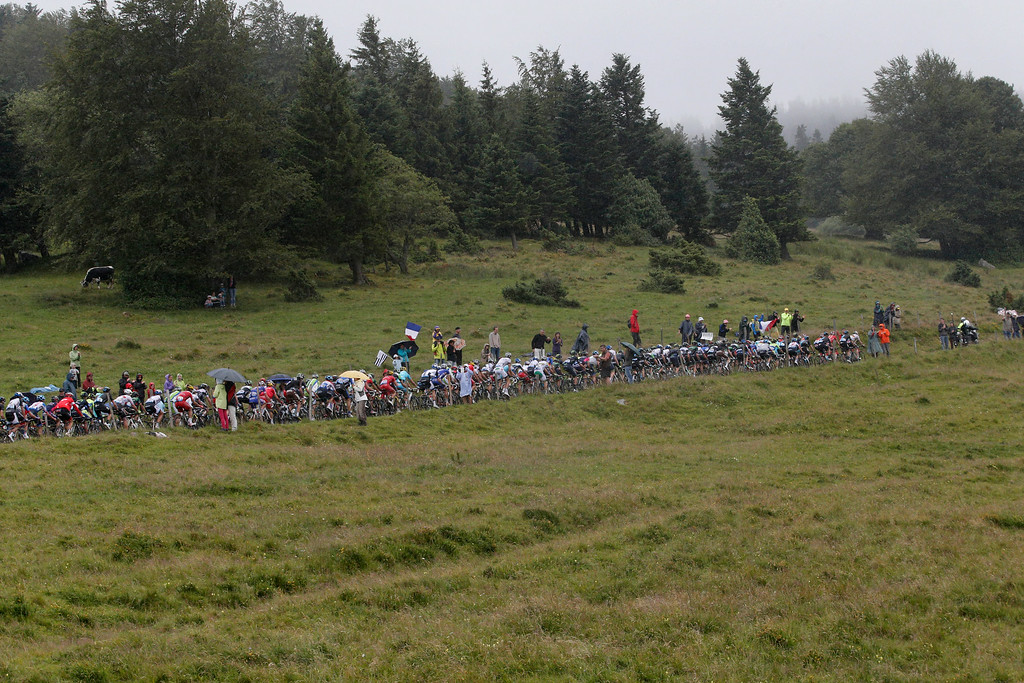 . The pack climbs during the tenth stage of the Tour de France cycling race over 161.5 kilometers (100.4 miles) with start in Mulhouse and finish in La Planche des Belles Filles, France, Monday, July 14, 2014. (AP Photo/Christophe Ena)