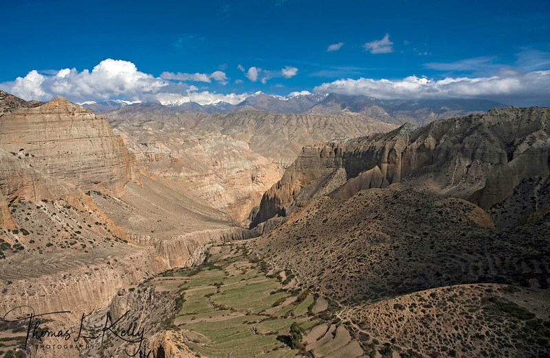 Pastureland and agricultural field against rugged mountains in Samar. Mustang, Nepal.