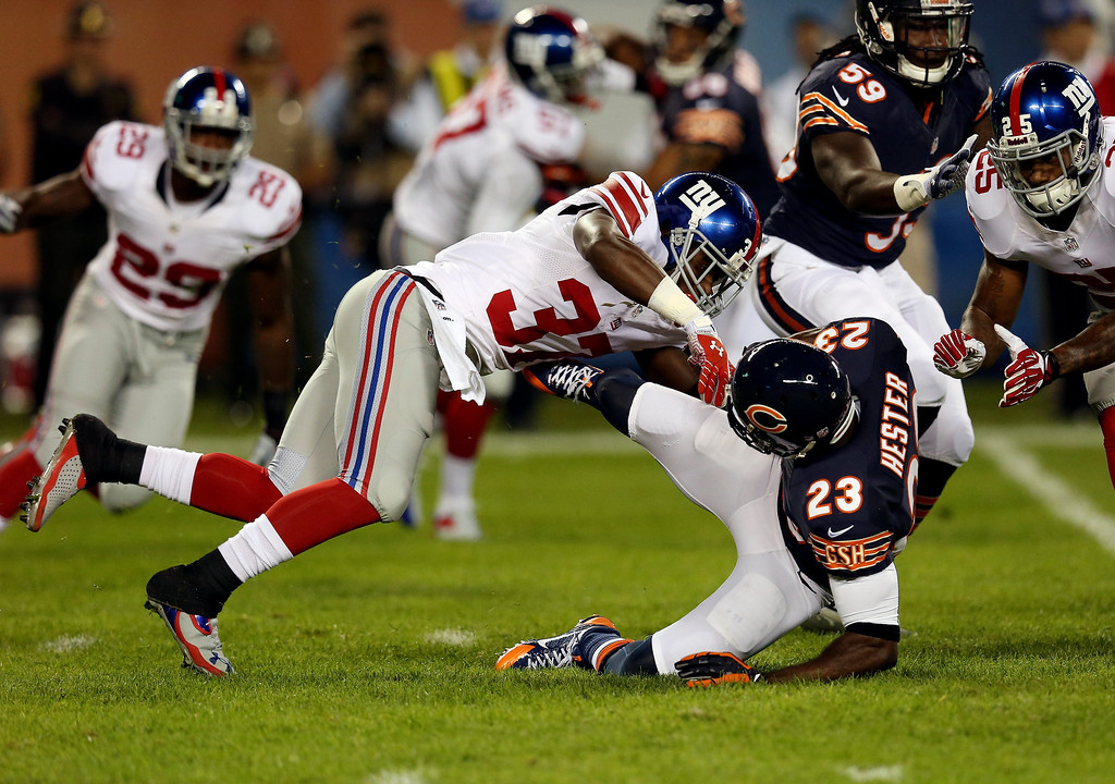 . Wide receiver Devin Hester #23 of the Chicago Bears is tackled by defensive back Charles James #37 of the New York Giants during a game at Soldier Field on October 10, 2013 in Chicago, Illinois.  (Photo by Jonathan Daniel/Getty Images)