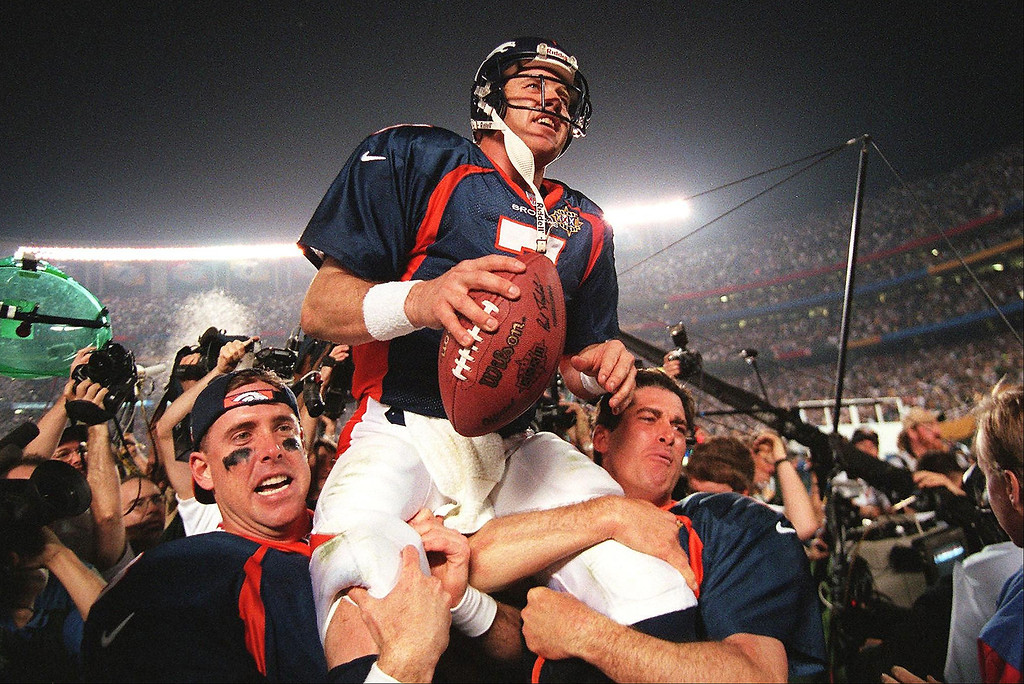 . Denver Broncos quarterback John Elway (C) is carried by teammates Ed McCaffrey (L) and Bubby Brister (R) after the Broncos defeated the  Green Bay Packers 31-24 to win Super Bowl XXXII in San Diego, CA 25 January.    (TIMOTHY A. CLARY/AFP/Getty Images)