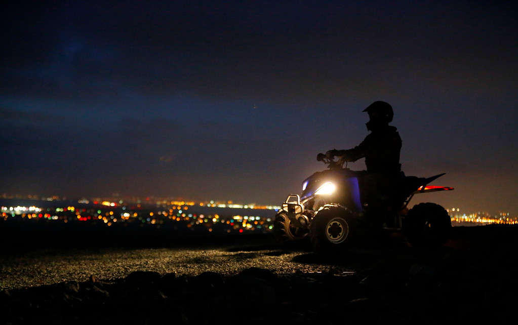. A U.S. Customs and Border Patrol agent waits at the top of a hill overlooking Imperial Beach, California, during his patrol along the international border between Mexico and the United States,  March 26, 2013. Picture taken March 26, 2013. REUTERS/Mike Blake