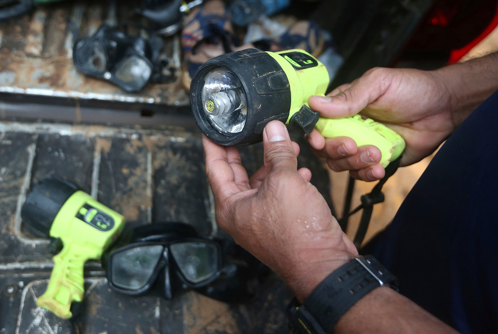 . In this Tuesday, July 3, 2018, file photo, a rescuer prepares a light for diving to reach the 12 boys and their soccer coach found alive in a flooded cave in Mae Sai, Chiang Rai province, northern Thailand. (AP Photo/Sakchai Lalit)