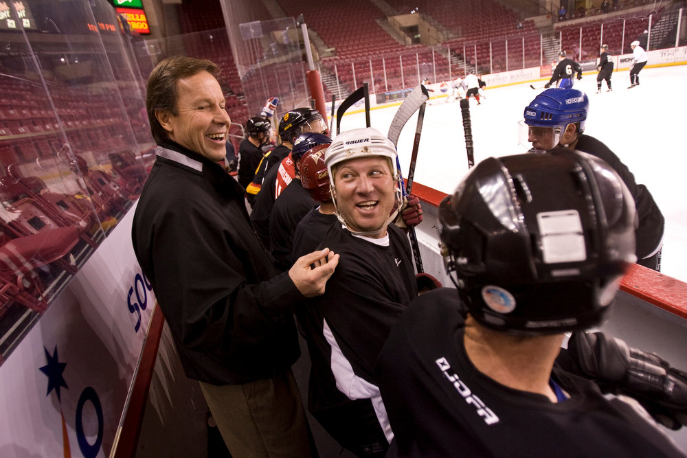 . The University of Denver celebrates 60 years from their hockey program with an alumni game with former players.  Friends and family sat and watch the former players play a game and joke with old friends and teammates Saturday afternoon. Here current DU coach, George Gwozdecky, speaks with former player, Don Mercier, who played from 1983-1986 during a break in Saturday\'s game. (Nathan W. Armes/Special to The Denver Post)