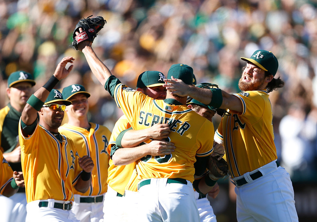 . Oakland Athletics\' Evan Scribner, center, is congratulated by Chris Young, left, and Derek Norris , right, after defeating the Minnesota Twins 11-7 in a baseball game to become American League West champions, Sunday, Sept. 22, 2013, in Oakland, Calif. (AP Photo/Beck Diefenbach)