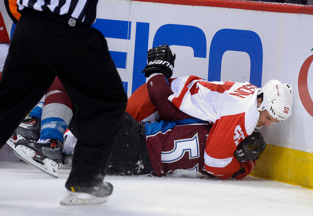 . Colorado Avalanche left wing Cody McLeod (55) gets tackled by Detroit Red Wings defenseman Jonathan Ericsson (52) after McLeod put a big hit on Detroit Red Wings defenseman Niklas Kronwall (55) up against the boards during the first period October 17, 2013 at Pepsi Center. Niklas Kronwall was taken off the ice by stretcher. (Photo by John Leyba/The Denver Post)