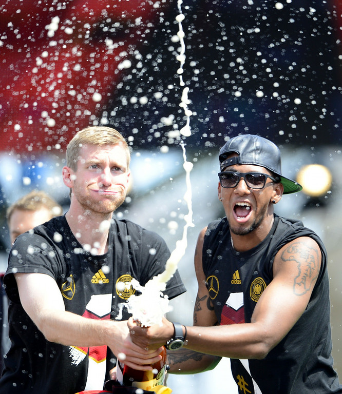. Germany\'s national football team\'s defender Per Mertesacker (L) and Germany\'s defender Jerome Boateng spray sparkling wine as they celebrate their FIFA World Cup 2014 title at a victory parade in front of fans on July 15, 2014 at Berlin\'s landmark Brandenburg Gate. Germany won their fourth World Cup title, after 1-0 win over Argentina on July 13, 2014 in Rio de Janeiro in the FIFA World Cup Brazil final game. (ROBERT MICHAEL/AFP/Getty Images)