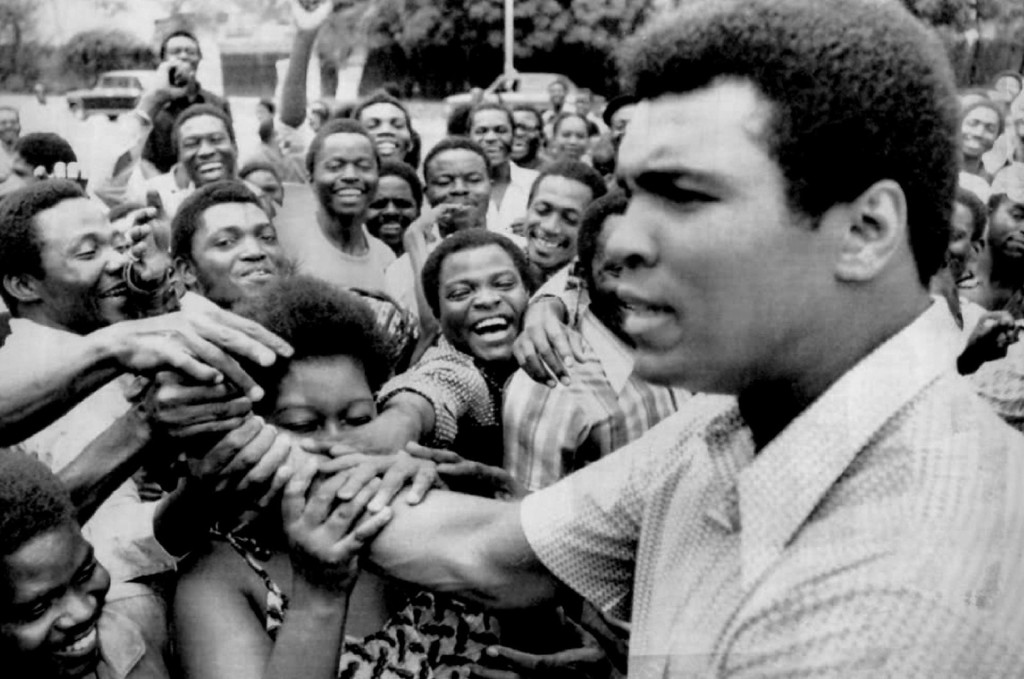 . Zaire admirers grab the arm of Muhammad Ali when he stopped in downtown Kinshasa during his sightseeing tout Tuesday morning. 1974. Denver Post Library photo archive