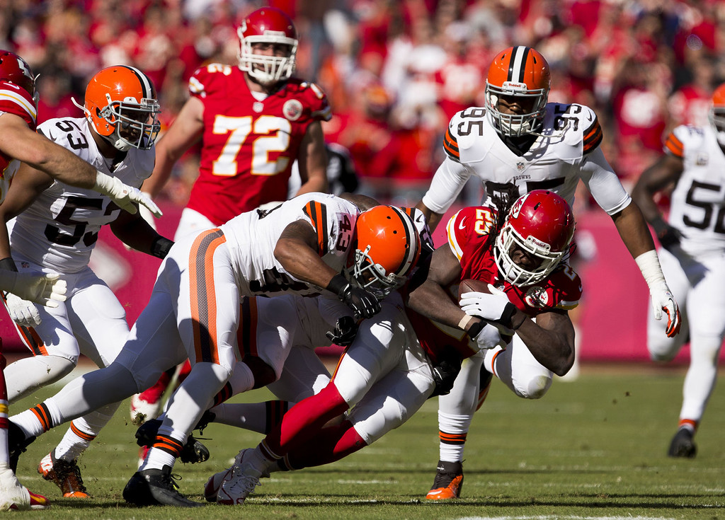 . Running back Jamaal Charles #25 of the Kansas City Chiefs is taken down by strong safety T.J. Ward #43 and free safety Tashaun Gipson #39 of the Cleveland Browns during the game at Arrowhead Stadium on October 27, 2013 in Kansas City, Missouri. (Photo by David Welker/Getty Images)