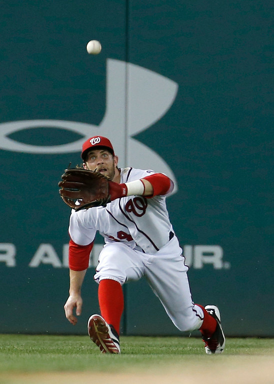 . Washington Nationals left fielder Bryce Harper lunges to catch a ball hit by Colorado Rockies\' Charlie Blackmon during the seventh inning of a baseball game at Nationals Park, Wednesday, July 2, 2014, in Washington. The Nationals won 4-3, and swept the three-game series with the Rockies. (AP Photo/Alex Brandon)