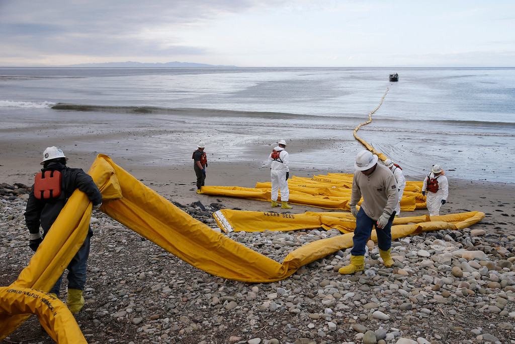 . Workers prepare an oil containment boom at Refugio State Beach, north of Goleta, Calif., Thursday, May 21, 2015. More than 7,700 gallons of oil has been raked, skimmed and vacuumed from a spill that stretched across 9 miles of California coast, just a fraction of the sticky, stinking goo that escaped from a broken pipeline, officials said. (AP Photo/Jae C. Hong)