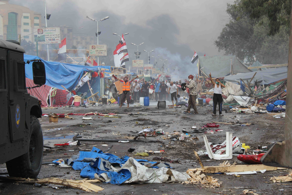 . Supporters of ousted Islamist President Mohammed Morsi, stand among debris and smoke in background as they confront Egyptian security forces trying to clear the smaller of the two sit-ins, near the Cairo University campus in Giza, Cairo, Egypt, Wednesday, Aug. 14, 2013. Egyptian security forces, backed by armored cars and bulldozers, moved on Wednesday to clear two sit-in camps by supporters of the country\'s ousted President Mohammed Morsi, showering protesters with tear gas as the sound of gunfire rang out at both sites. (AP Photo/Imad Abdul Rahman)