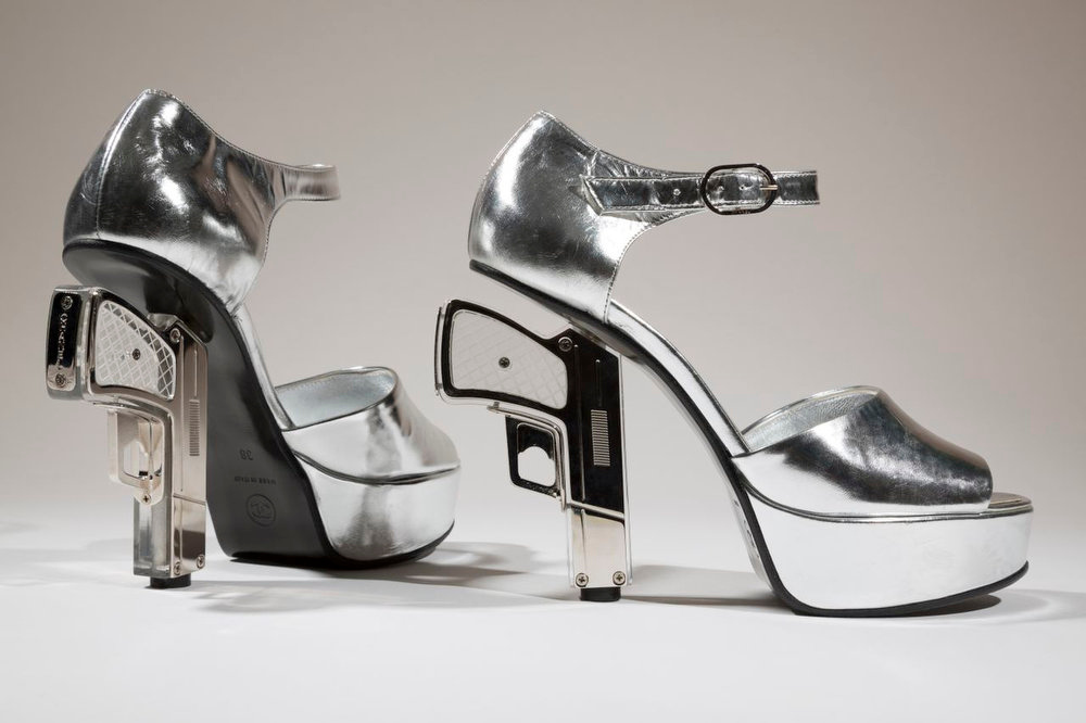 Description of . A pair of silver shoes designed by Chanel with guns as heels. The shoe is on display at the