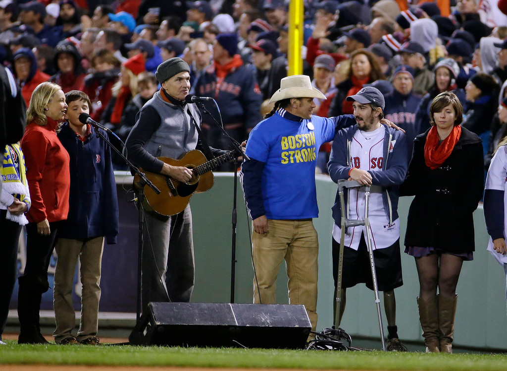 ". James Taylor sings ""God Bless America\"" alongside Carlos Arredondo, center, and Boston Marathon bombing survivor Jeff Bauman, second from right, during the seventh inning stretch of Game 2 of baseball\'s World Series between the Boston Red Sox and the St. Louis Cardinals Thursday, Oct. 24, 2013, in Boston. (AP Photo/Matt Slocum)"