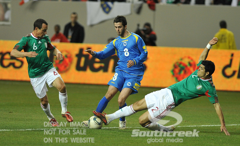 Mexico's Defender Francisco Rodriguez (#2) and Mexico's Midfielder Gerardo Torrado (#6) attempt to take the ball away from Bosnia-Herzegovina's Midfielder Miralem Pjanic (#8) in Soccer action between Bosnia-Herzegovina and Mexico.  Mexico defeated Bosnia-Herzegovina 2-0 in the game at the Georgia Dome in Atlanta, GA.
