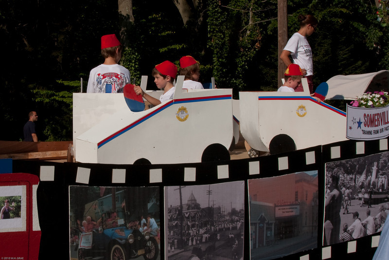 (1) Pslip Slug #: 66990; (2) West Ridgewood Avenue and Monroe Avenue, Ridgewood, NJ; (3) 07/05/10; (4) Participants line up and make final preparations for the 100th annual Ridgewood Independence Day Parade on 7/5/2010; (5) (L-R) Rob, Parker and their Somerville classmates Cooper and Stephen demonstrate an example of Ridgewood's 100 years of tradition on Somerville's float, lined up to begin the 100th annual Ridgewood 4th of July Parade on 7/5/2010; (6) W.H. Grae for the Ridgewood News.
